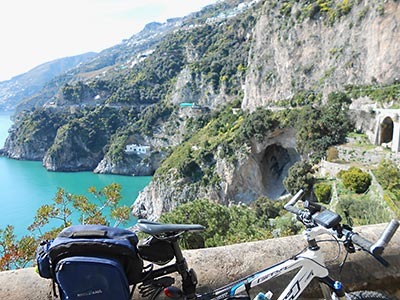 Picture of a bike with the Conca dei Marini coast road in the background.