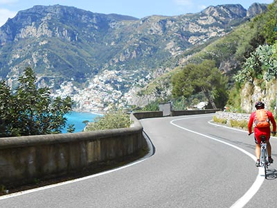Picture of a cyclist riding towards Positano.